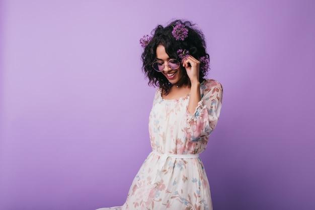 Ujmująca afrykańska dziewczyna pozuje w sukience z kwiatowym wzorem. portret beztroskiej czarnej damy z aliumami we włosach.