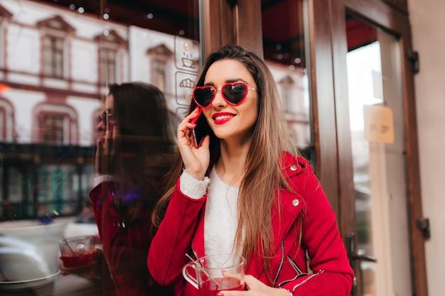 Ujmująca dama o brązowych włosach rozmawia przez telefon w pobliżu kawiarni