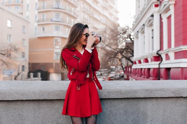 Ujmująca dziewczyna w czerwonej spódnicy robi zdjęcia wiosennego miasta