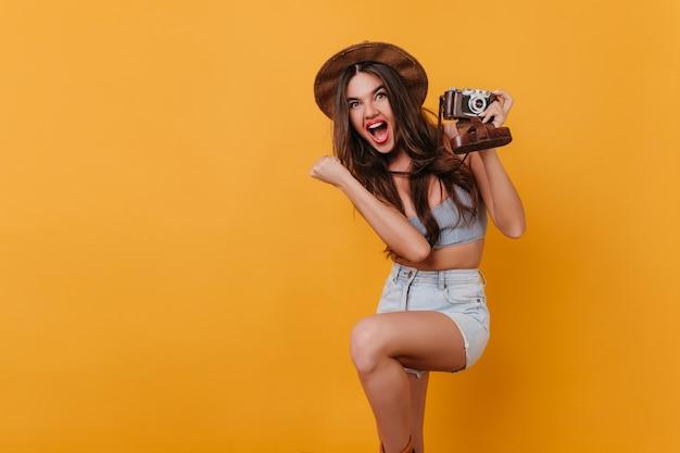 Ujmująca dziewczyna w eleganckim brązowym kapeluszu, taniec i trzymając aparat