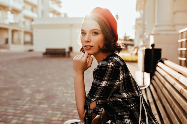 Ujmująca dziewczyna w francuskim berecie siedzi w parku. odkryty zdjęcie eleganckiej kaukaskiej pani chłodzi na ławce.