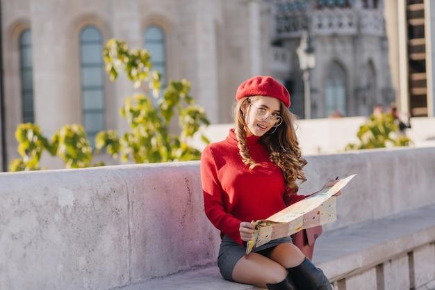 Ujmująca dziewczyna w krótkiej spódnicy siedzi na kamiennej ławce z mapą miasta