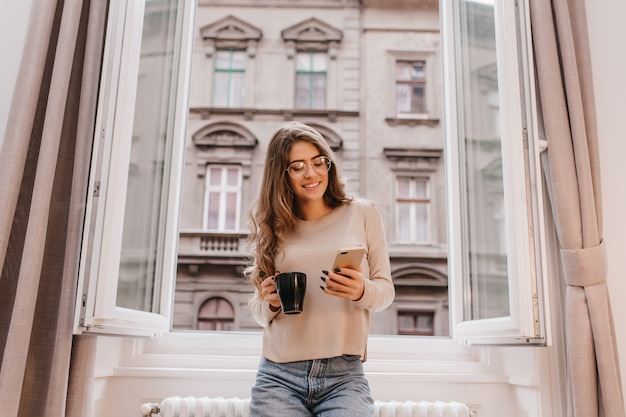Ujmująca dziewczyna w swobodnym stroju spędza czas w domu i pozuje na tle miasta przy filiżance herbaty