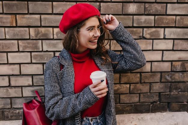 Ujmująca dziewczyna w vintage tweedowy płaszcz, trzymając okulary i odwracając wzrok z uśmiechem