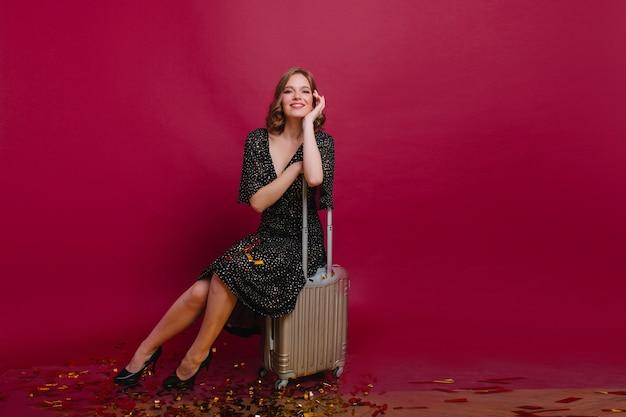 Ujmująca dziewczyna w wysokich obcasach siedzi na walizce po imprezie z przyjaciółmi