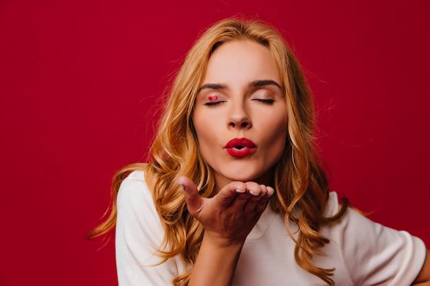 Ujmująca dziewczynka kaukaski wyrażająca miłość na czerwonej ścianie. urocza blondynka wysyłająca pocałunek w powietrze.