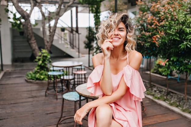 Ujmująca jasnowłosa dziewczyna w romantycznej sukience siedzi w ulicznej kawiarni. entuzjastyczna młoda kobieta pozuje w restauracji z roślinami
