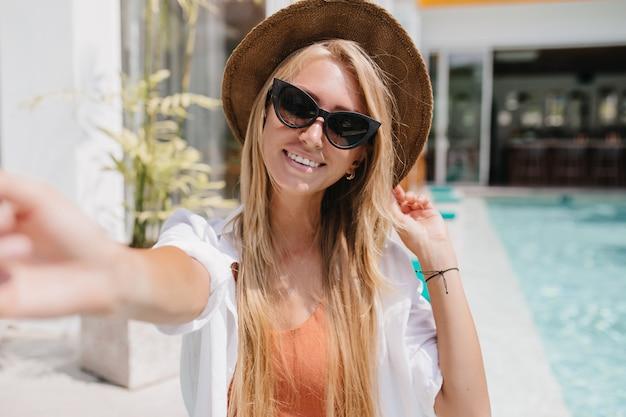 Ujmująca jasnowłosa kobieta uśmiecha się podczas robienia selfie w letni dzień. spektakularna blondynka w okularach przeciwsłonecznych robi sobie zdjęcie przed basenem.