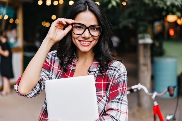 Ujmująca kaukaski dziewczyna w okularach pozuje po zajęciach. zewnątrz zdjęcie wesoły studentka z laptopem.