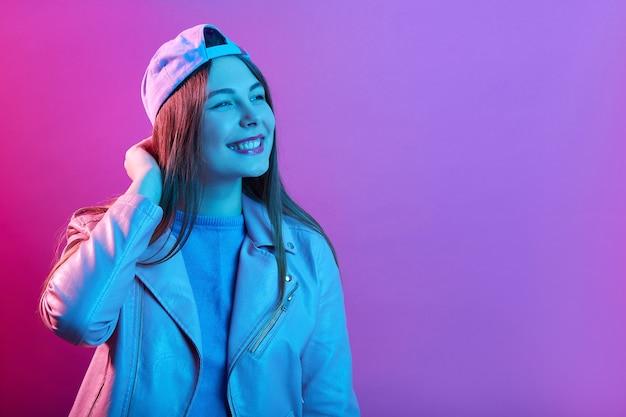 Ujmująca kobieta stoi uśmiechnięta, piękna dziewczyna w czapce i skórzanej kurtce, wesoły młody model dotykając jej głowy i patrząc na bok