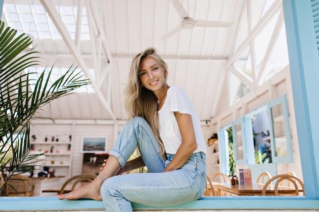 Ujmująca kobieta z łagodnym uśmiechem siedząca na parapecie rano. zainteresowana blondynka w dżinsach vintage pozowanie w kawiarni.