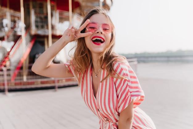 Ujmująca modelka w klasycznej sukience w paski, taniec w parku rozrywki. zewnątrz portret błogiej kobiety blondynka w okularach przeciwsłonecznych stojących w pobliżu karuzeli ze znakiem pokoju.