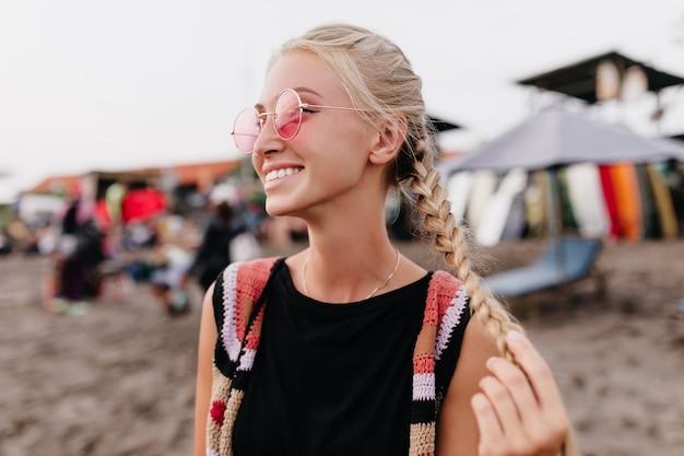 Ujmująca opalona kobieta pozuje z uśmiechem na plaży. zewnątrz portret blondynki w różowe okulary, grając z jej warkoczykami.