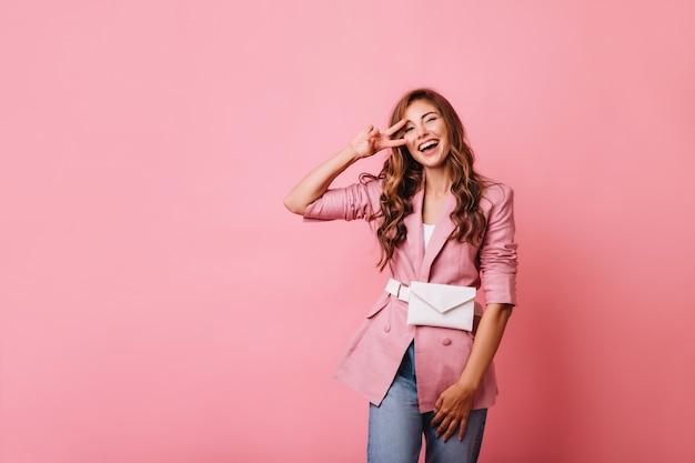 Ujmująca ruda kobieta pozuje z czarującym uśmiechem. kryty portret atrakcyjnej kręconej dziewczyny w różowej kurtce.
