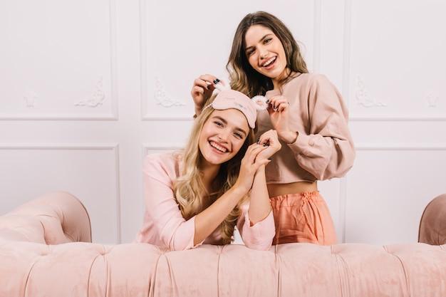 Ujmujące kobiety w piżamie pozują na różowej kanapie