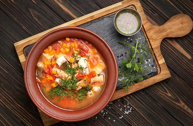 Ukha po królewsku, zupa rybna z kilku odmian ryb, w glinianym talerzu, na drewnianej desce