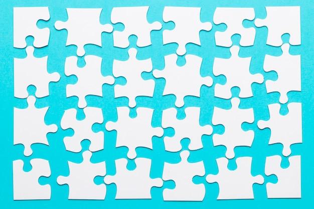 Układ biały kawałek układanki na niebieskim tle