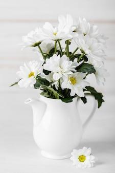 Układ białych kwiatów w białym wazonie