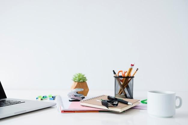 Układ biurka z laptopem i notebookami