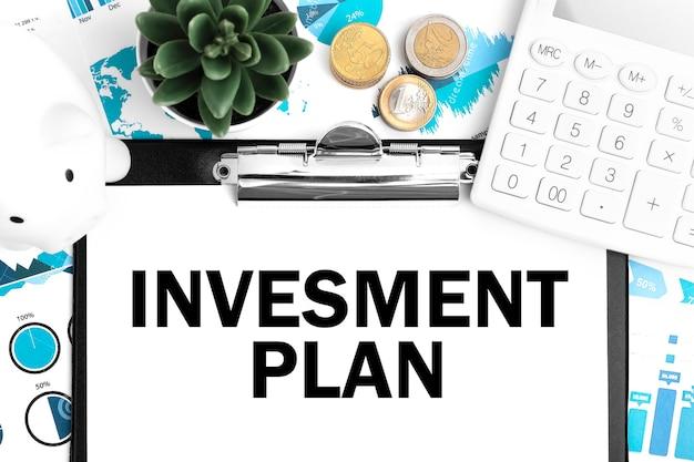Układ biznesowy. tekst plan inwestycyjny w schowku. kalkulator, świnka, moneta, wykresy i wykresy.