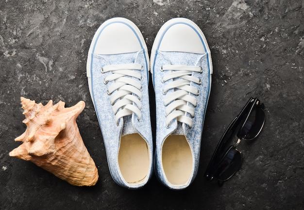 Układ butów i akcesoriów plażowych na czarnej betonowej podłodze. modne trampki, muszla, okulary przeciwsłoneczne. leżał płasko.