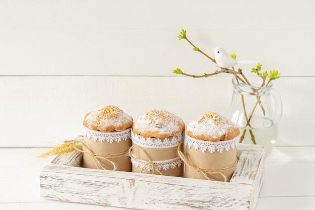 Układ dekoracji wesołych świąt wielkanocnych koncepcja tło wakacje. ciasta wielkanocne w drewnianym pudełku i wiosenne gałązki. pastelowe kolory.