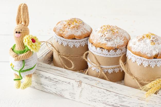 Układ dekoracji wesołych świąt wielkanocnych koncepcja tło wakacje. ciasta wielkanocne w drewnianym pudełku z ręcznie robionym króliczkiem na drutach. pastelowe kolory.