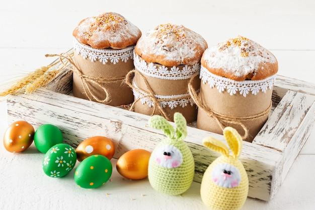 Układ dekoracji wesołych świąt wielkanocnych koncepcja tło wakacje. wielkanocne ciasta w drewnianym pudełku z ręcznie robionymi jajkami. pastelowe kolory.