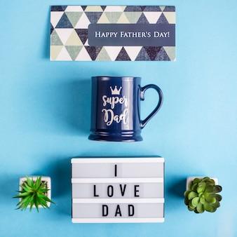 Układ dnia ojca z filiżanką prezentu, kartą i napisem kocham tatę