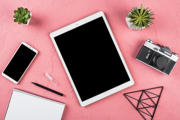 Układ elementów biurowych na różowym tle