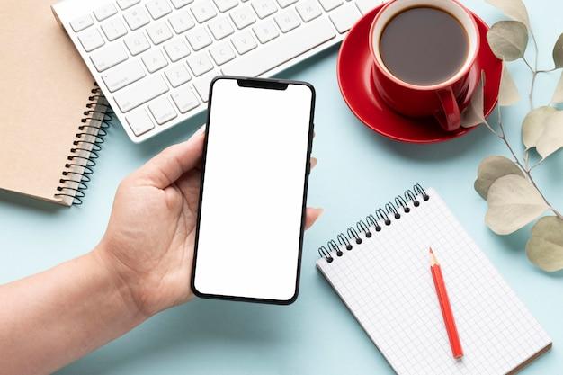 Układ elementów biurowych pod wysokim kątem z pustym ekranem telefonu