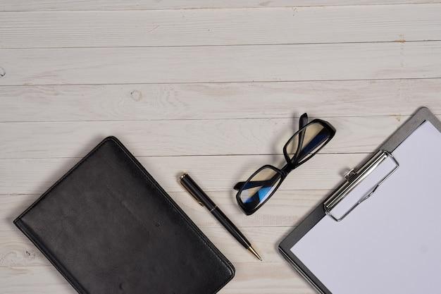 Układ elementów biznesowych na stole, teczka na okulary biała kartka papieru