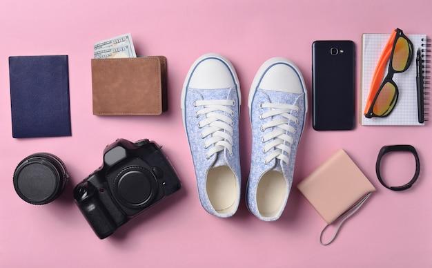 Układ gadżetów i akcesoriów na różowym pastelowym tle. trampki, sprzęt fotograficzny, torebka z dolarami, inteligentny zegar, smartfon, notatnik, okulary przeciwsłoneczne. pojęcie podróży, przedmioty, widok z góry