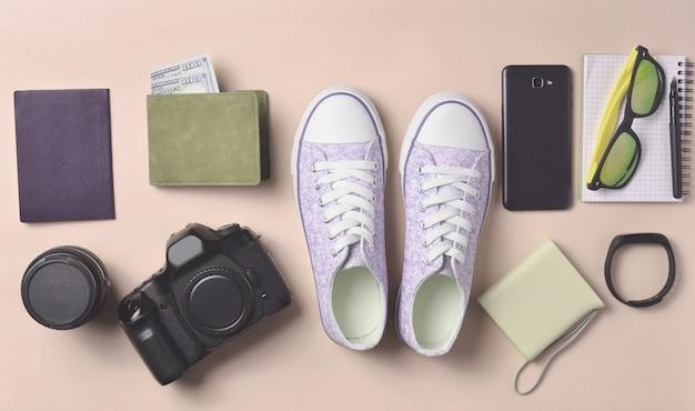 Układ gadżetów i akcesoriów na różowym pastelowym tle. trampki, sprzęt fotograficzny, torebka z dolarami, inteligentny zegar, smartfon, notatnik, okulary przeciwsłoneczne