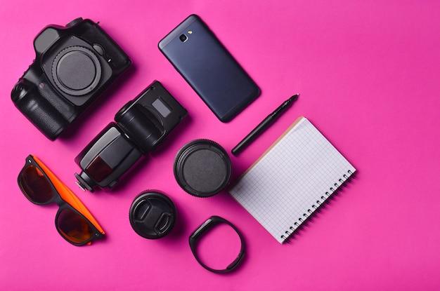 Układ gadżetów i akcesoriów na różowym tle. sprzęt fotograficzny, inteligentny zegar, smartfon, notatnik, okulary przeciwsłoneczne. pojęcie podróży, obiektów, widok z góry