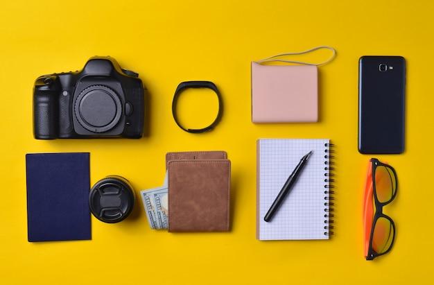 Układ gadżetów i akcesoriów na żółtym tle. power bank, sprzęt fotograficzny, torebka z dolarami, inteligentny zegar, smartfon, notatnik, okulary przeciwsłoneczne. pojęcie podróży, obiektów, widok z góry