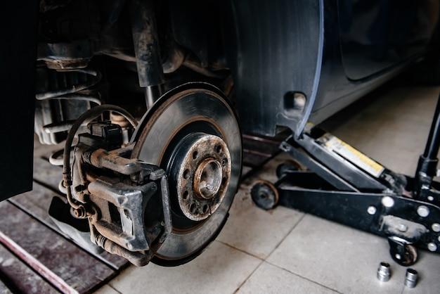 Układ hamulcowy samochodu, z tarczą hamulcową i klockiem hamulcowym. naprawa zawieszenia samochodu w garażu.