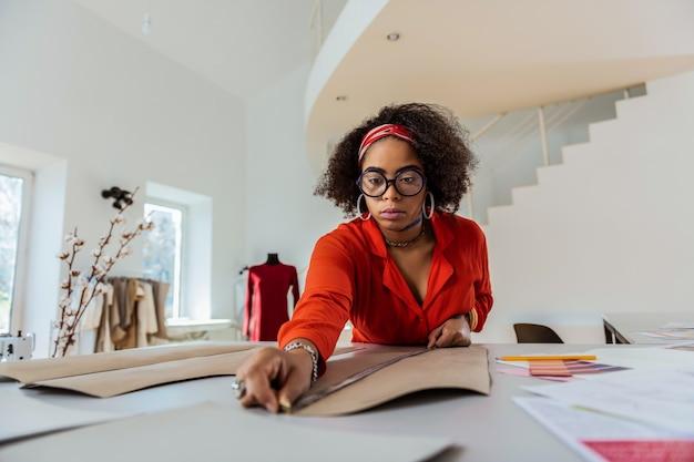 Układ kartonowy. koncentruje się african american girl w czerwonym stroju mierzącym właściwą długość z długą linijką