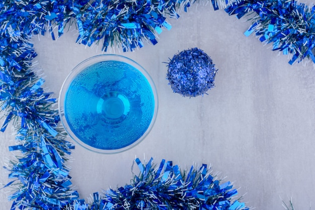 Układ kieliszka koktajlowego i niebieskich ozdób choinkowych na białym tle.