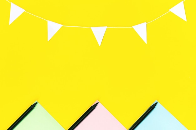 Układ kolorowego papieru, czarnych ołówków i girlandy z białych flag umieszczonych na żółtym tle.