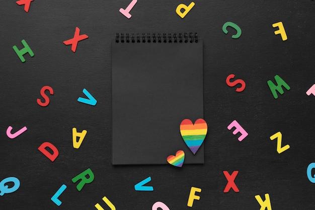Układ kolorowych liter z góry i wyśrodkowany notatnik
