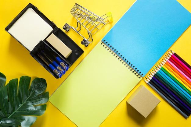 Układ kolorowych papeterii na spiralnym notesie na żółtym tle, kolorowe kredki. business flat lay, back to school