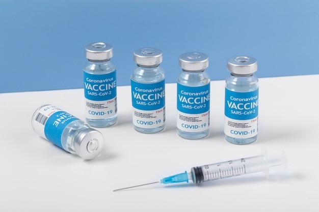 Układ koronawirusa z butelką ze szczepionką i strzykawką