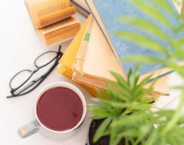 Układ książek z filiżanką i szklankami