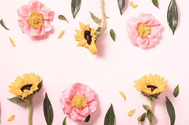 Układ kwiatów w stylu płaski na pastelowym różowym tle. minimalistyczny charakter flatlay. kreatywne lato płaskie i widok z góry tło.
