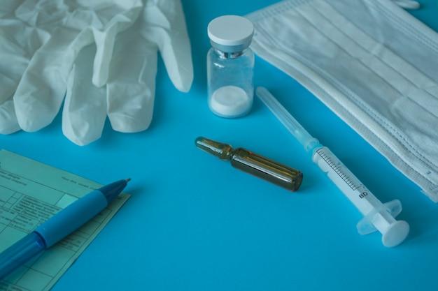 Układ medyczny. fiolka szczepionki i strzykawka do wstrzykiwań, maska medyczna i rękawiczki, recepta. koncepcja szczepienia koronawirusowego