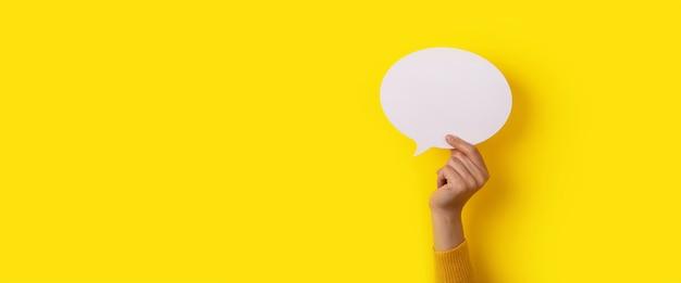 Układ mowy bąbelkowej w ręku na żółtym tle, makieta panoramiczna