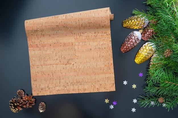 Układ na temat nowego roku 2022 z arkuszem pergaminu, zabawkami i gałęziami choinki na ciemnym tle.