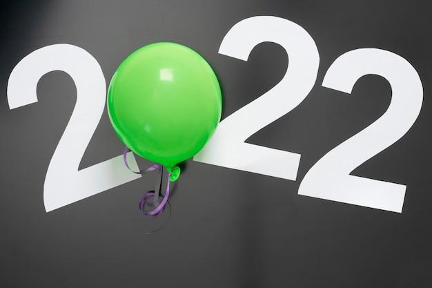 Układ na temat nowego roku 2022 z numerami, piłką, zabawkami na ciemnym tle.
