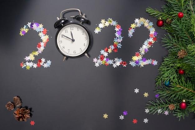 Układ na temat nowego roku 2022 z numerami, zegarami, zabawkami i gałęziami choinki na ciemnym tle.